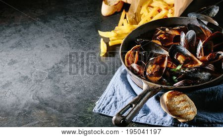 Shell mussels in a frying pan in tomato sauce, French fries and croutons on a dark background. Lots of copy space