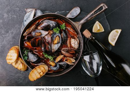 Mussels in a frying pan in tomato sauce, croutons and bottle of wine on dark background. Top view.