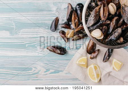 Shells of washed mussels in a colander and slices of lemon on a wooden background. Top view. Copy space.