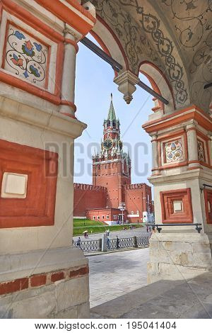 View on Moscow Red Square Kremlin tower Spasskaya Bashnya with Chiming Kuranti Clock through arch of Saint Basil Cathedral church. Moscow Kremlin Red Square Popular famous sightseeing tours places