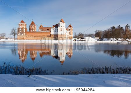 Mir Castle in Minsk region is ancient heritage of Belarus reflected in lake. UNESCO World Heritage. Winter scene with snow.