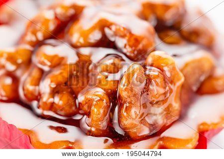 Walnut cake with caramel and honey. Close up on white background.