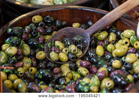 Olives with serving spoons in wooden bowls being sold on local grocery market.