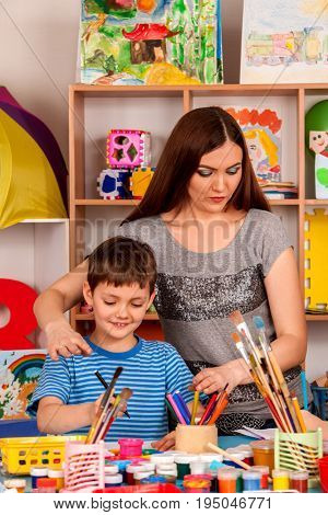 Small student boy with teacher painting in art school class. Child color by paints on table. Mom praises son in kindergarten. Craft drawing education develops creative abilities of children.