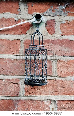 Old brick wall and black candle holder with water in the garden.