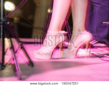 Feet of a girl on stilettos on stage .