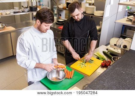 cooking food, profession and people concept - happy male chef cook with knife peeling carrot and chopping cucumber on cutting board at restaurant kitchen
