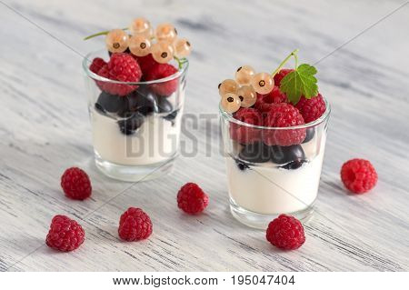 Yogurt with raspberries and currants in a small glass. Black currant, white currant.