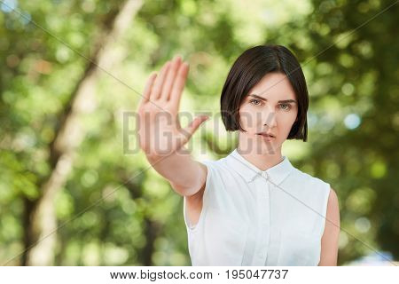 An attractive and confident woman in a bright park. Elegant girl with brunette hair rejecting an offer on a natural light green background. Serious business lady straightens out her hand.