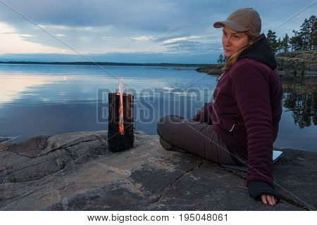 A woman sits on the shore of a large lake on a large rock near a burning Finnish candle