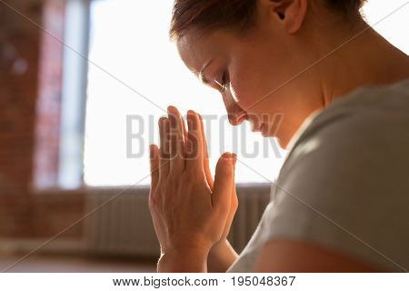 religion, faith and people concept - close up of woman meditating at yoga studio or praying