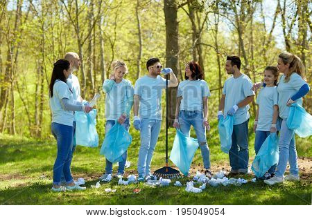 volunteering, charity, cleaning, people and ecology concept - group of happy volunteers with garbage bags and rake talking in park