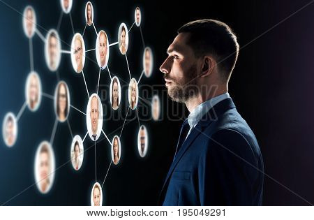 business, people, corporate, headhunting and technology concept - businessman in suit looking at contacts network over black background