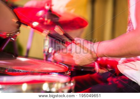 Musician plays drums in a rock band .