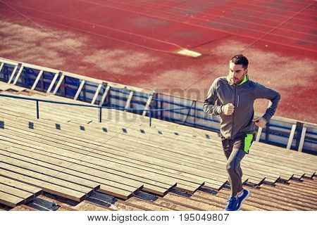 fitness, sport, exercising and people concept - young man running upstairs on stadium
