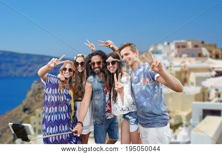 tourism, travel, technology and people concept - happy hippie friends in sunglasses taking picture by smartphone on selfie stick and showing peace gesture over oia town on santorini island background