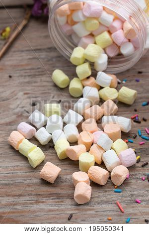 Pink and white mini marshmallows in a jar on an old rustic wooden table with space for text. Mini white and pink puffy marshmallows. Marshmallow concept