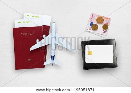 Air tickets passports credit card money and toy plane on table