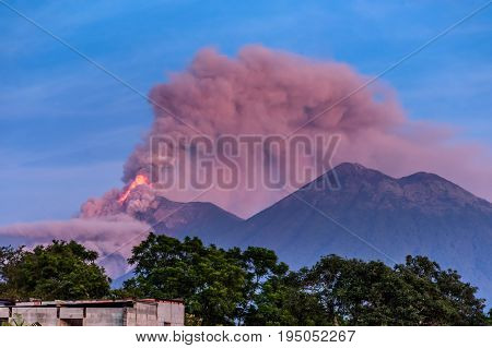 Lava & smoke spurt from erupting Fuego volcano next to Acatenango volcano at dawn near Antigua, Guatemala, Central America
