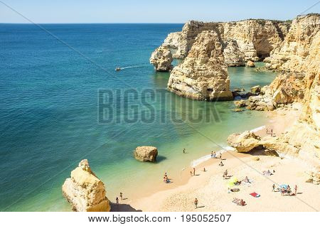 Bay with tourists at Praia da Marinha, Beautiful Portuguese coast to swim, Favorite Portuguese sunbathing destination, Bay in Portugal Algarve