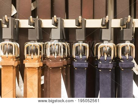 Different men's belts with buckles on the boutique showcase