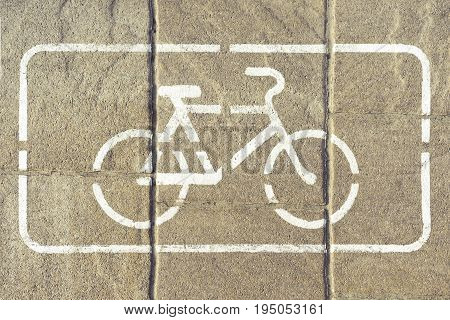 Bicycle lane. Bike path with a symbol of a white bike in a white rectangle. Bicycle sign on gray asphalt pavement close up view