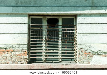 Old window with broken glass and bars on abandoned house with damaged facade plaster.