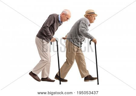 Full length profile shot of two elderly men with canes walking isolated on white background