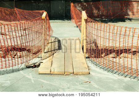 Improvised wooden bridge over the trench on the street construction site for pedestrians and orange construction safety fence.