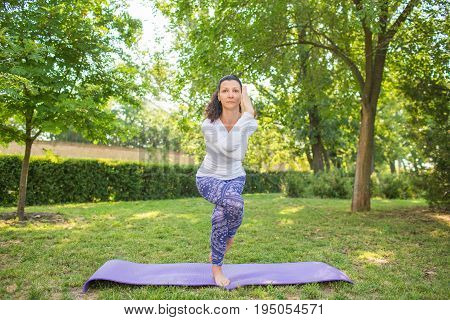 The gorgeous young woman is practising yoga pose in the green park with a lot of trees and bushes. A lady is looking sporty and doing sports exercise. The sports exercises  for health.