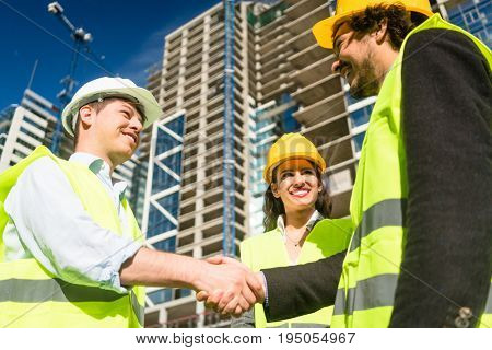 Architects and foreman in meeting at construction site of high-riser