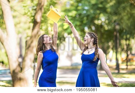 Two charming gorgeous, beautiful girls in blue dresses in the park. A beautifully looking girl with a left holds a  book in her hands. An elegant lady with the right has beautiful pigtails. Cute girls