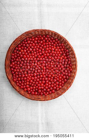 Beautiful nutritious currant in a brown wooden basket on a grey background. Tasteful red ripe currant in a crate. Healthful breakfast for vegetarians.