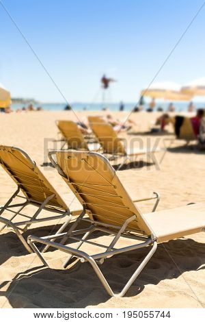closeup of some beige sunloungers and some beige umbrellas in a beach in the Mediterranean sea, with many unrecognizable people sunbathing in the background