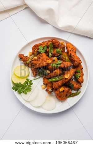 Chicken 65 - spicy deep fried Bar appetizer or quick snack from India in a bowl or plate over white background, selective focus