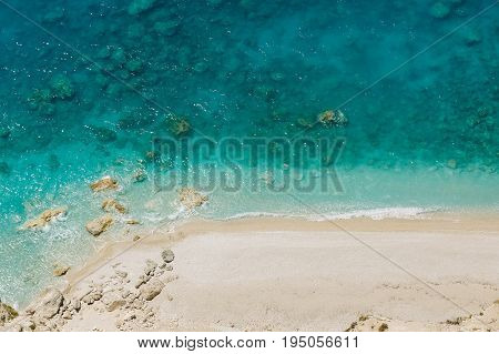 Aerial view to pristine beach with rocky bay and waves crashing