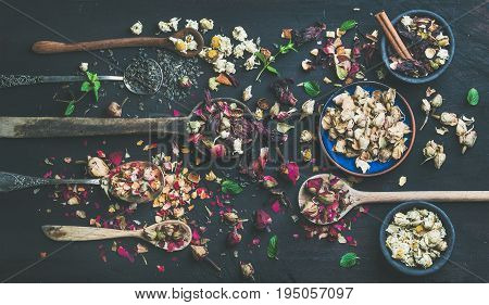 Wooden spoons with dry herbs, flower buds and tea leaves over black scorched wooden background, top view, horizontal composition