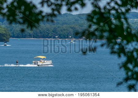 Waterskiing on the lake with a waterboard and a pontoon boat during summer vacation