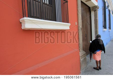 Colorful old woman and houses in Antigua, Guatemala, Central America. The historic city Antigua is UNESCO World Heritage.