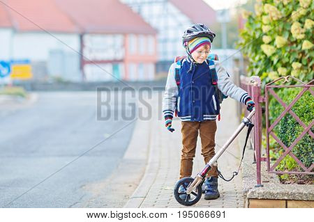 Active school kid boy in safety helmet riding with his scooter in the city. Happy child in colorful clothes biking on way to school. Safe way for kids outdoors to school.