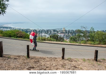 Parachute downhill skateboarder catching wind on hill overlooking city of Ventura.