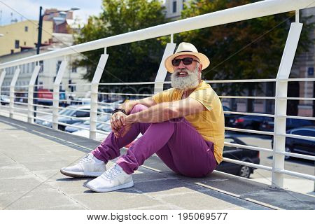 Close-up shot of senior man leaning arms on knees while sitting in downtown