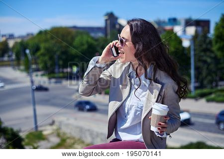 Mid shot of pleasant brunet talking on phone while holding cup of coffee