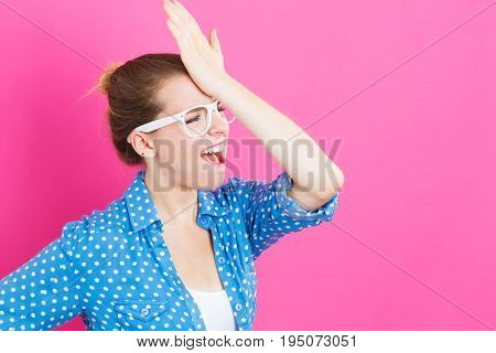 Young woman making a mistake on a pink background