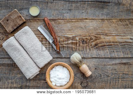 Preparing for men shaving. Shaving brush, razor, foam on wooden table background top view.