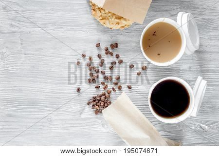 Coffee to go. Coffee cups with cover and coffee beans on wooden table backound top view.
