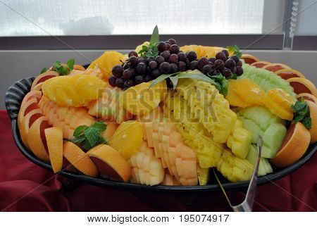 Tropical fruit platter served in black circular tray with silver tongs