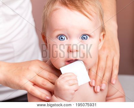 Seven month baby girl's shoulder joints being manipulated by an osteopath, an alternative medicine treatment. Child is holding blank card in mouth looking at camera