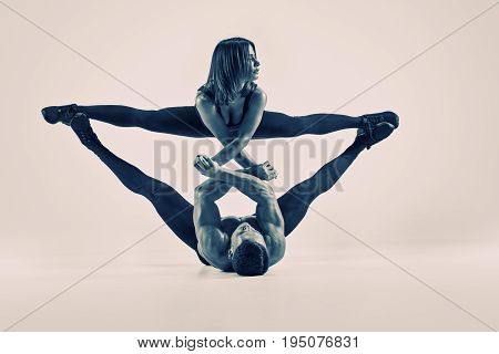 Two young sporty acrobats practising supporting exercises, black and white picture with split toning