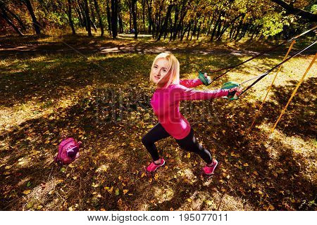 Top view photo of young woman doing workout with fitness straps in park
